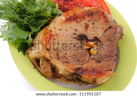 Delicious Pork Chop with Tomatoes and Greens close up on plate isolated on white background