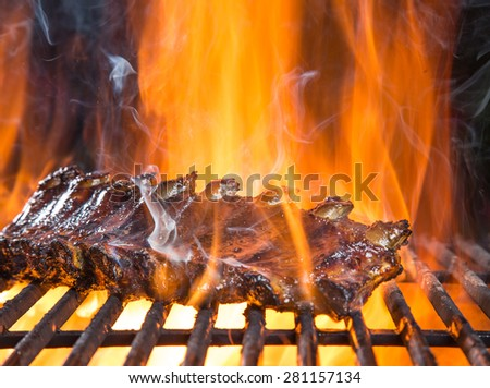 Delicious pork spareribs on cast-iron grill grate, garden barbecue. - stock photo