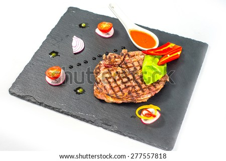 Delicious portion of healthy grilled lean medium rare beef steak cut through and served on a board garnished with fresh herbs - stock photo