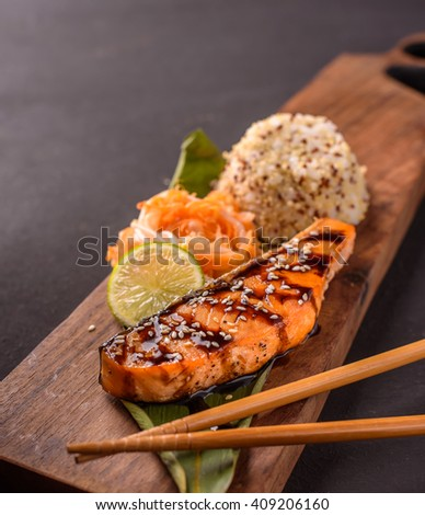 Delicious portion of trout with rice, carrots and lemon on a dark background - healthy food - stock photo