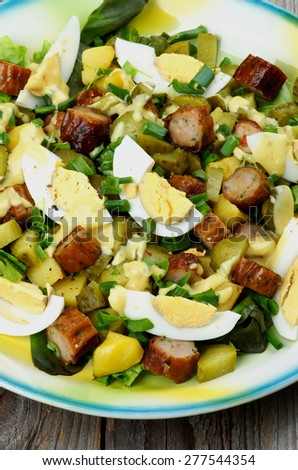 Delicious Potato and Sausage Salad with Gherkins, Lettuce, Boiled Eggs and Mustard Sauce closeup on Yellow and Blue Plate - stock photo