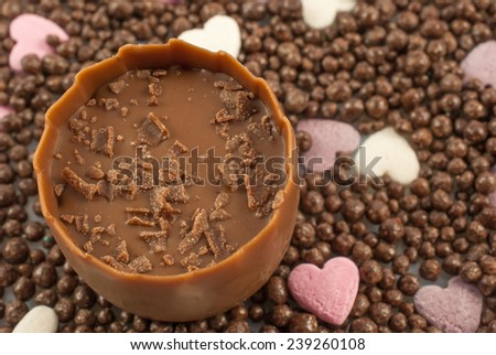 Delicious praline garnished with milk chocolate flakes on chocolate balls and small sugar hearts as background - stock photo