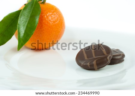 Delicious pralines coated in smooth dark chocolate on plate on white background - stock photo