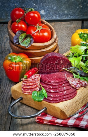 Delicious prosciutto and salami slices on wooden chopping board with vegetables and herbs. Culinary traditional ham. - stock photo
