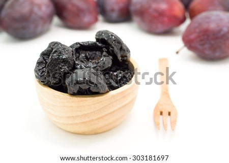 Delicious prunes in wooden bowl and fresh plums on background