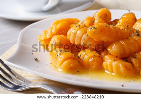 Delicious pumpkin gnocchi with butter and spices on the plate closeup. horizontal  - stock photo