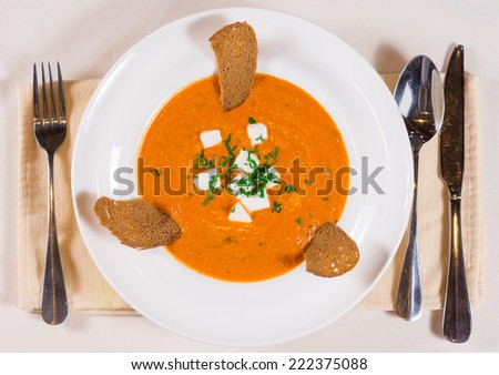 Delicious pumpkin or butternut soup with cheese, melba toast and fresh herbs, overhead view in a white bowl with cutlery alongside - stock photo