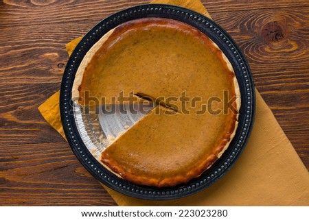 Delicious Pumpkin Pie on a Decorative Wooden Table - stock photo