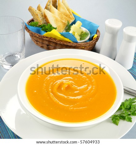 Delicious pumpkin soup with a selection of toasts with butter. - stock photo