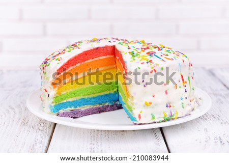 Delicious rainbow cake on plate on table on light background - stock photo