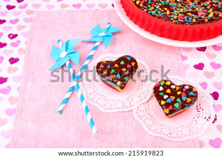 Delicious rainbow cakes on paper napkin, on bright background