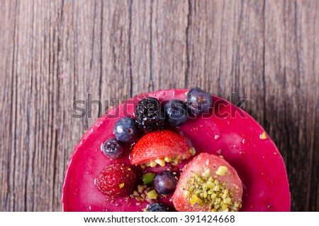 Delicious raspberry cake with fresh strawberries, raspberries, blueberry, currants and pistachios on wooden background. free space for your text. - stock photo
