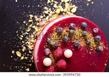 Delicious raspberry cake with fresh strawberries, raspberries, blueberry, currants and pistachios on black background.  - stock photo