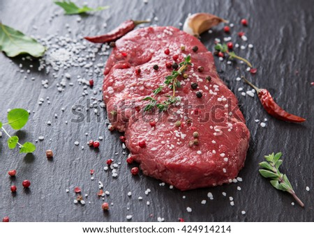 Delicious raw beef steak on black stone table, close-up. - stock photo