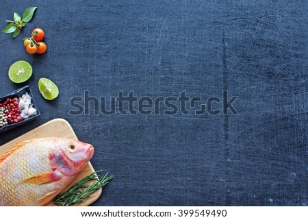 Delicious raw fish (Nile tilapia) on a wooden board with lime, herbs, spices and cherry tomato. Dark background. Copy space.  - stock photo