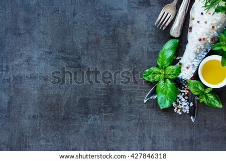 Delicious raw fish with olive oil, herbs and spices on dark vintage background, preparation. Flat lay. Healthy food or diet nutrition concept. - stock photo