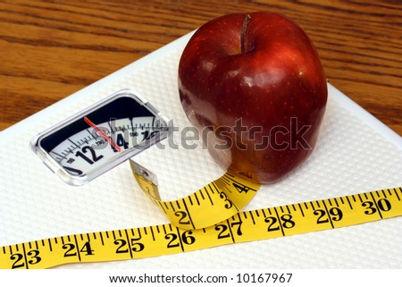 Delicious red apple on a scale with a tape measure.  The concept of eating healthy for good health. - stock photo