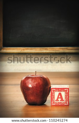 Delicious red apple on old school desk - stock photo