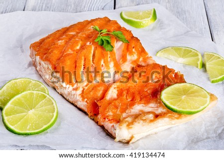 Delicious red fish salmon steak fillet on a white parchment paper on a wooden table,  studio lights, close-up - stock photo