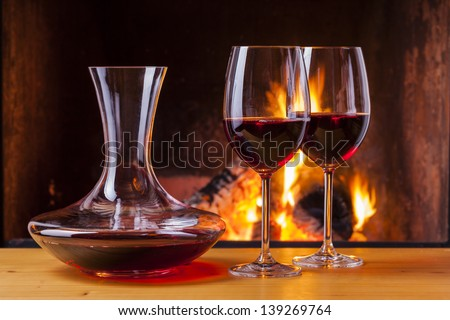 delicious red wine with decanter at romantic fireplace - stock photo