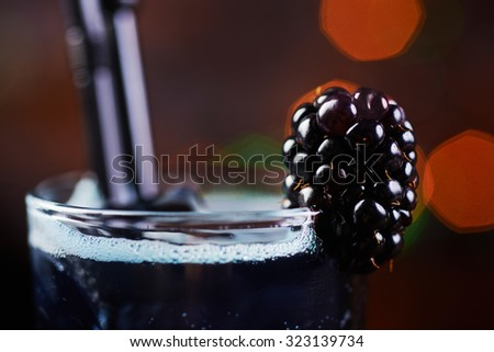 delicious refreshing blackberry alcoholic cocktail or lemonade in a glass on a table in a restaurant with backgrounds of bright disco lights. soft focus - stock photo