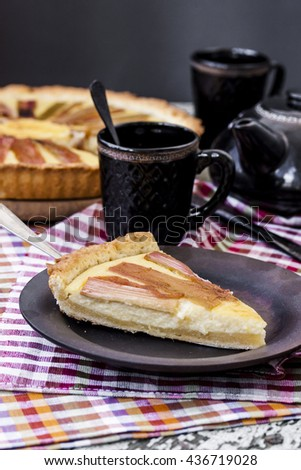 Delicious rhubarb pie with custard and on rustic background - stock photo