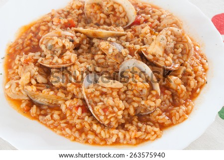 Delicious rice dish with clams sprinkled with parsley - stock photo