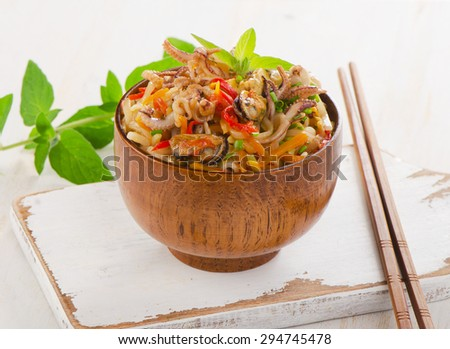 Delicious rice noodles with seafood closeup in a wooden bowl. Selective focus - stock photo
