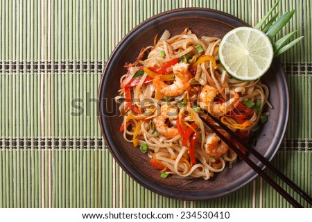 Delicious rice noodles with shrimp close-up on a plate. horizontal view from above  - stock photo