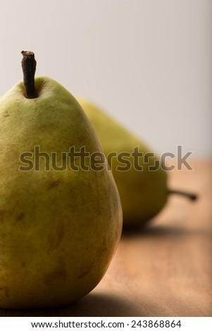 delicious, ripe pears on a wooden kitchen table, white background, closeup, vertical. - stock photo