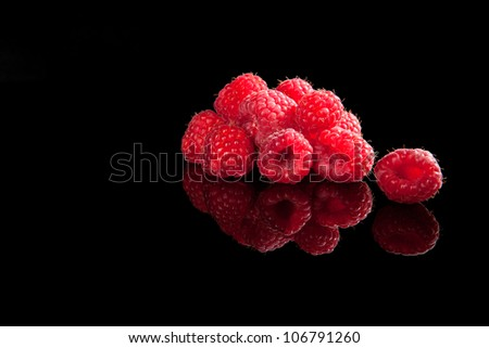 Delicious ripe raspberries isolated on black background with reflection. Luxurious fruit summer background. - stock photo