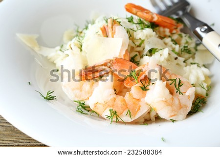 Delicious risotto with shrimp and dill on a plate, food close-up - stock photo