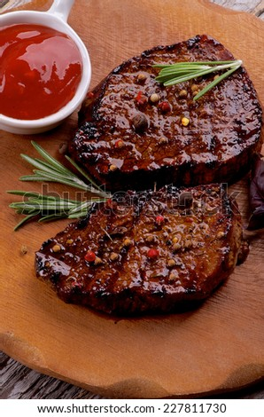 Delicious Roasted Beef Steaks with Spices and Tomato Sauce closeup on Wooden Plate  - stock photo
