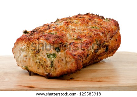 Delicious Roasted Brisket of Pork Baked in Herbs and Spices Full Body closeup on Wood Cutting Board - stock photo