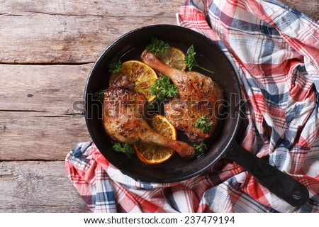 Delicious roasted duck leg with oranges and parsley in a pan close-up. top view, horizontal, rustic style  - stock photo