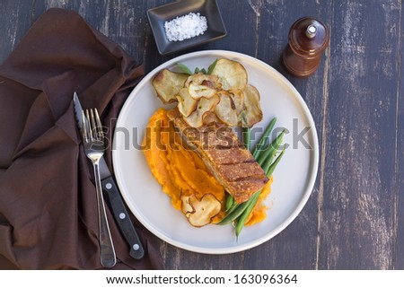 Delicious roasted pork belly with crackling, sweet potato mash, fried apple crisps and steamed green beans. - stock photo