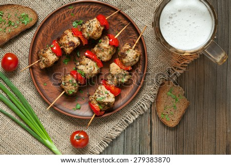 Delicious roasted turkey or chicken kebab skewers meat barbecue on clay dish with tomatoes, green onion, wholegrain bread and beer. Vintage textile and wooden background. Rustic style and natural - stock photo
