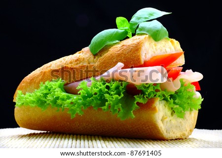 Delicious roll full of ham, paprika and lettuce - stock photo