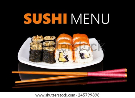 Delicious rolls served on plate isolated on black with space for your text - stock photo