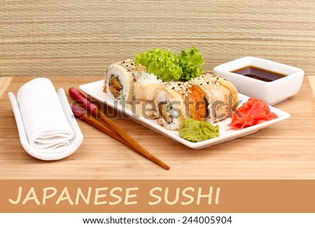 Delicious rolls served on plate on bamboo mat with space for your text - stock photo