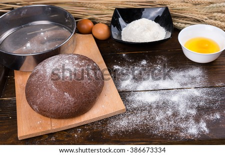 Delicious round loaf of baked rye bread on cutting board next to flour sifter, bowls and eggs on wooden table - stock photo