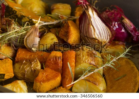 Delicious rustic baked vegetables with fresh rosemary straight from the oven in golden light. - stock photo