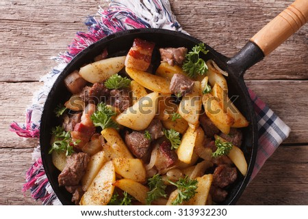 Delicious rustic fried potatoes with meat and bacon in a pan close-up. horizontal top view - stock photo
