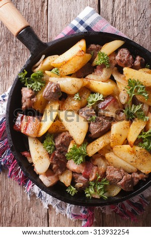 Delicious rustic fried potatoes with meat and bacon in a pan close-up. vertical top view - stock photo