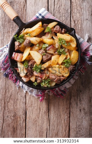 Delicious rustic fried potatoes with meat and bacon in a pan. vertical top view - stock photo