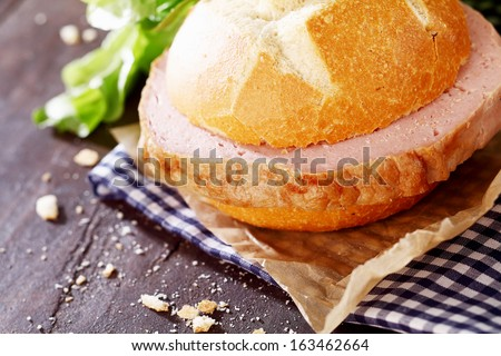 Delicious rustic lunch of a meat loaf sandwich with a crusty white rolled filled with a generous slice of German beef and pork loaf on a blue and white checkered napkin - stock photo
