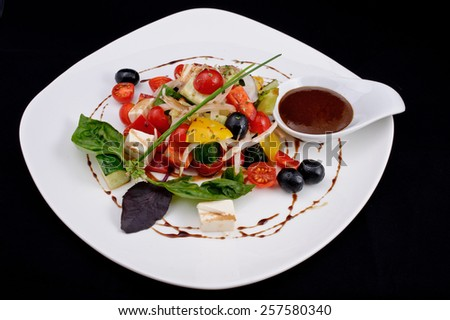 Delicious salad of cherry tomatoes, cheese, greens, cucumber, yellow pepper, olives, onion, sorrel, with brown sauce, decorated with drops of sauce. - stock photo