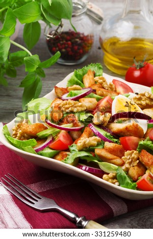 Delicious salad with chicken, nuts, egg and vegetables.
