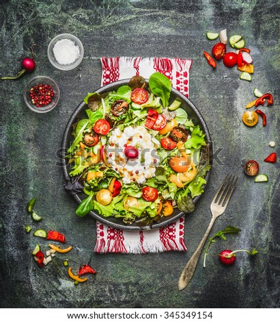 Delicious salad with cottage cheese and tomatoes, served on rustic background, top view - stock photo