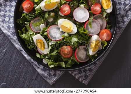 Delicious salad with eggs, radishes and sorrel close up on the table. horizontal view from above - stock photo